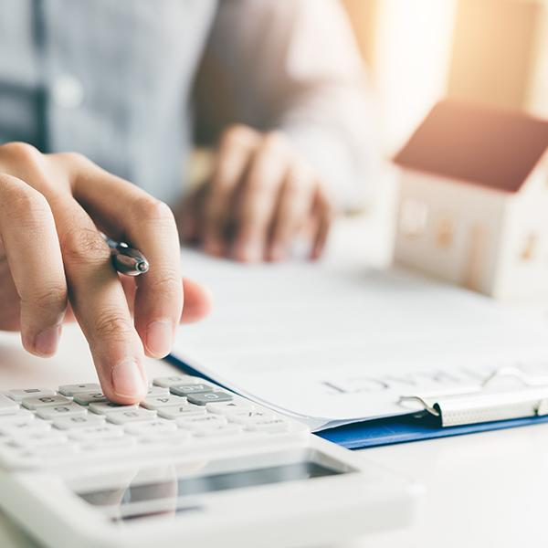 Osoba trzymająca wręce długopis używa kalkulatora