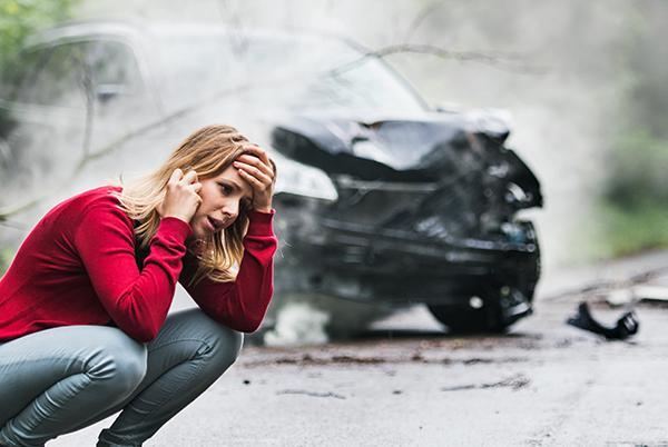 Kobieta kuca przed rozbitym samochodem irozmawia przez telefon