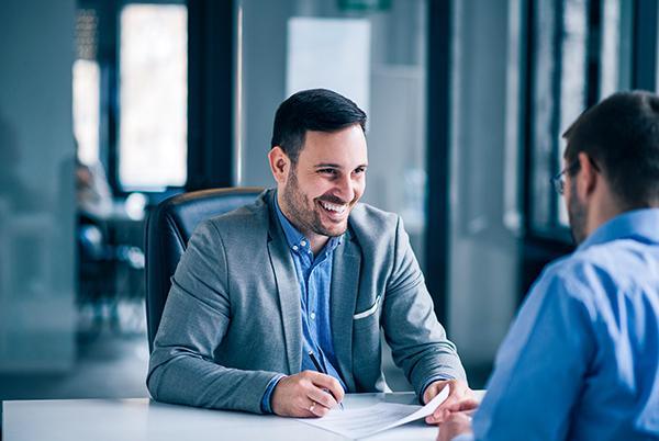 Uśmiechnięty mężczyzna wmarynarce rozmawia zdrugą osobą